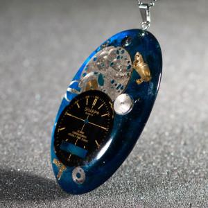 Duży wisior z częściami zegarków.