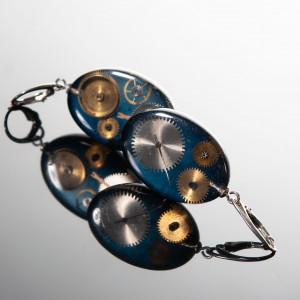 Kolczyki z częściami zegarków na niebieskim tle.
