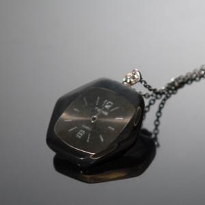 Sześciokątny wisior z częściami zegarków.