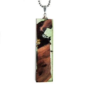 Wisior z transparentno-zielonej żywicy i drewna.